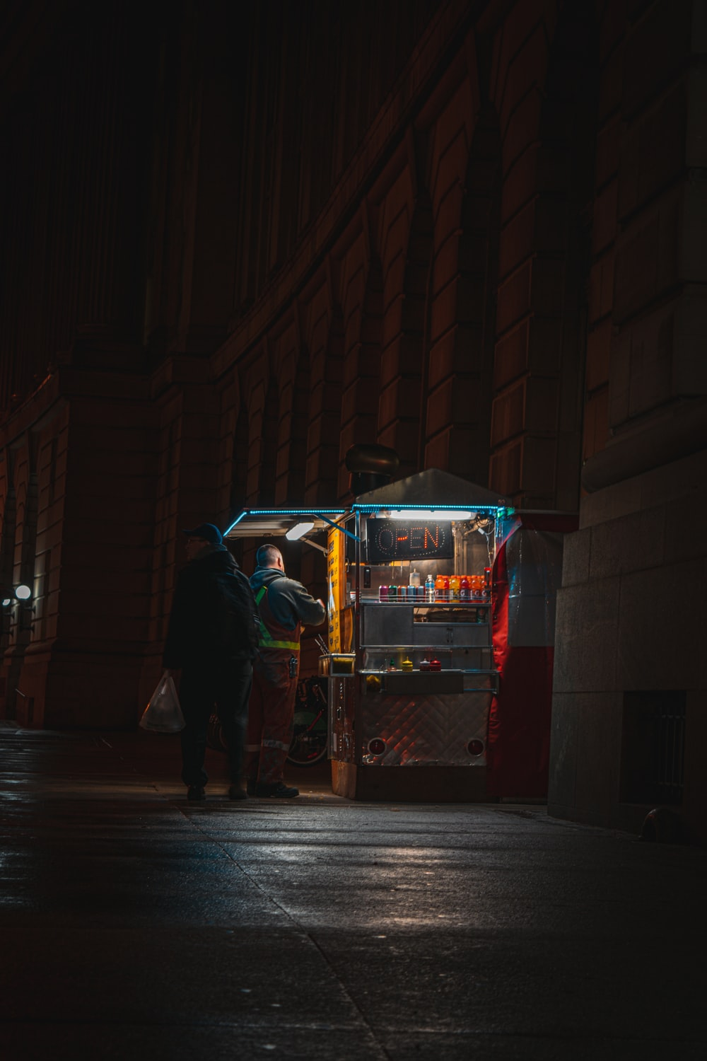 man in black jacket and black pants standing beside red and white food cart