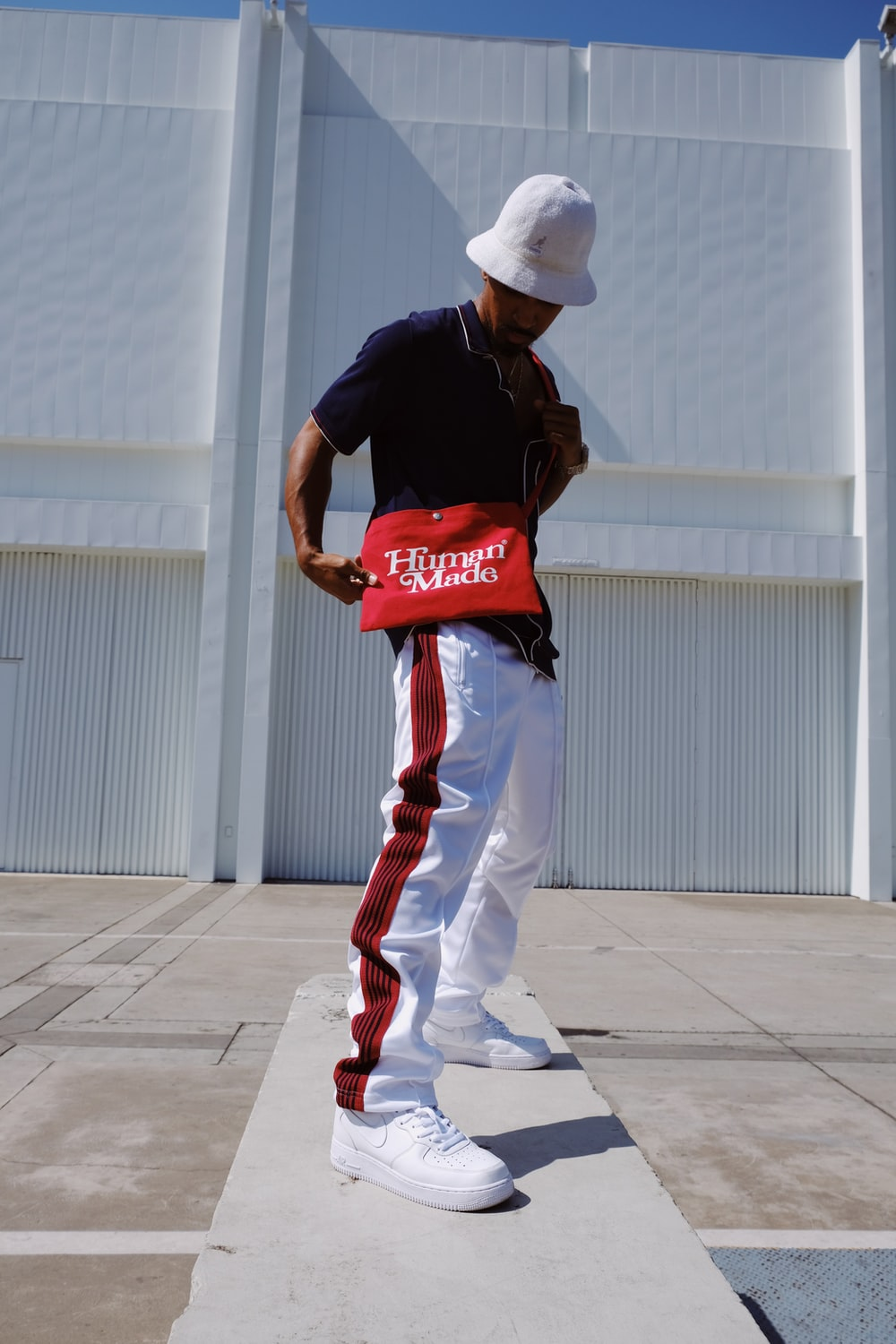man in red and white crew neck t-shirt and white pants