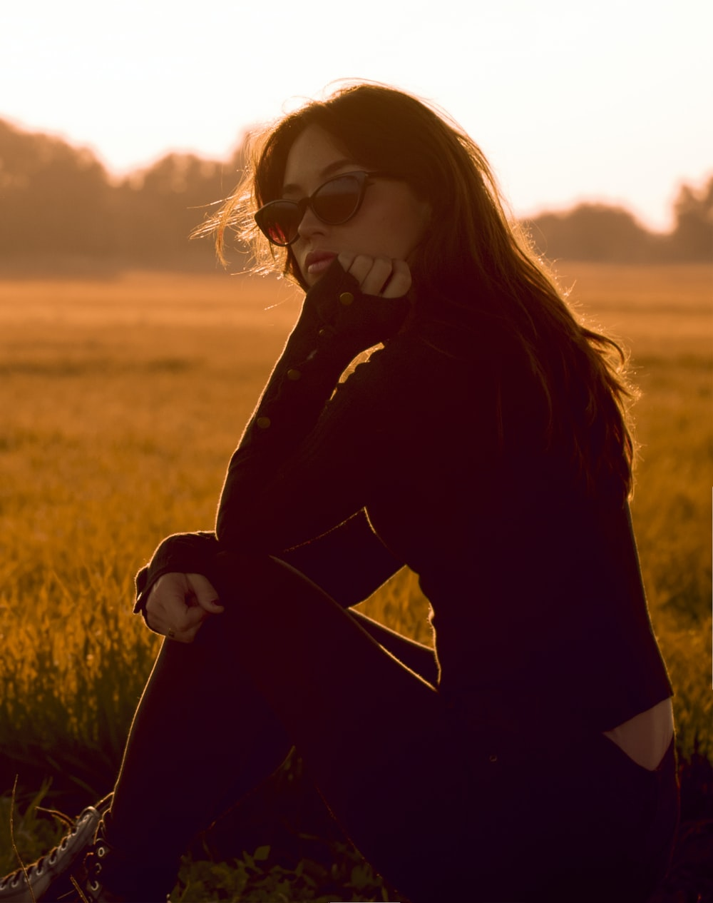 woman in black long sleeve shirt and black sunglasses standing on green grass field during daytime