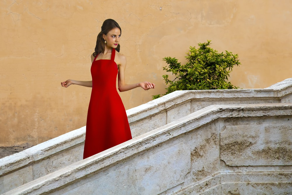 woman in red sleeveless dress standing on stairs