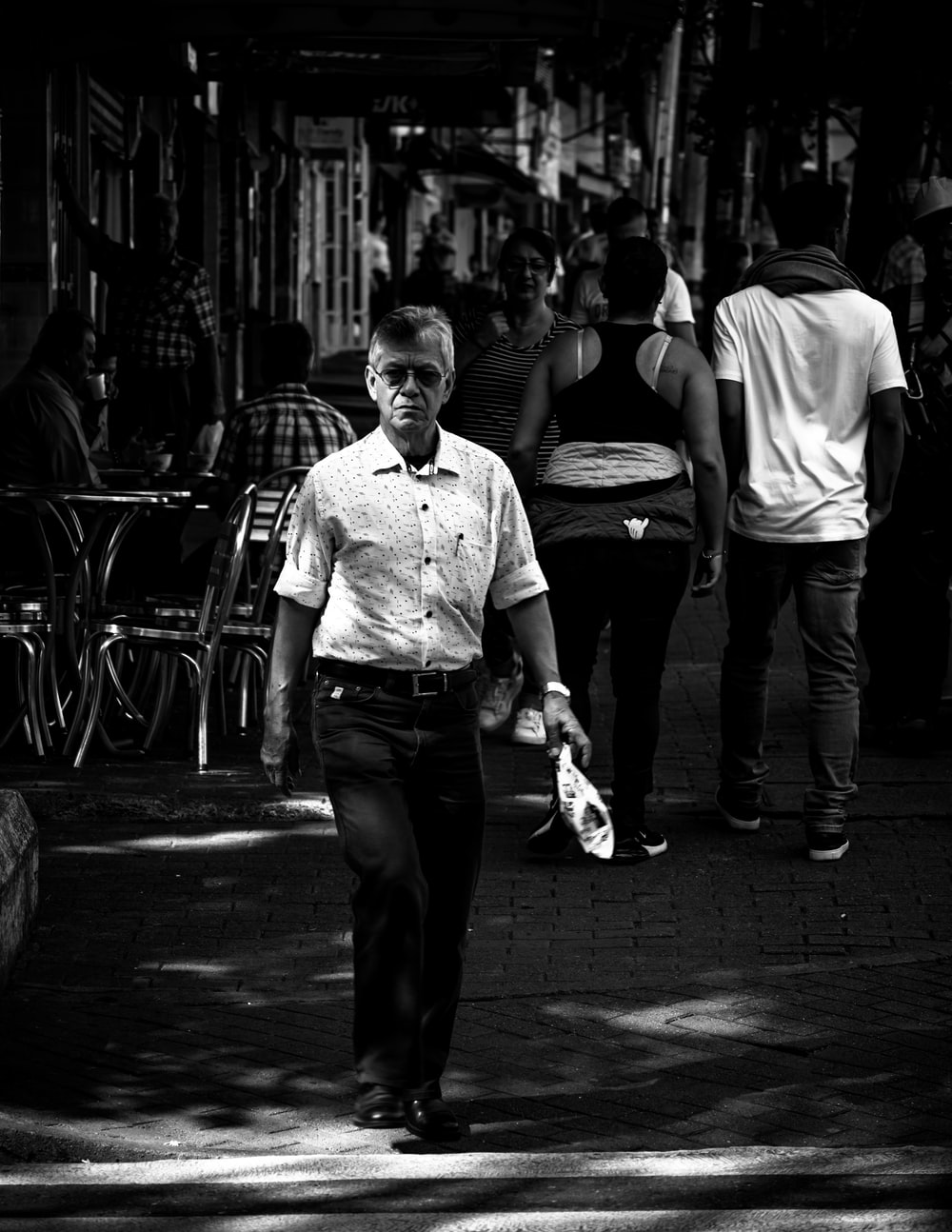 grayscale photo of man in dress shirt and pants standing on sidewalk