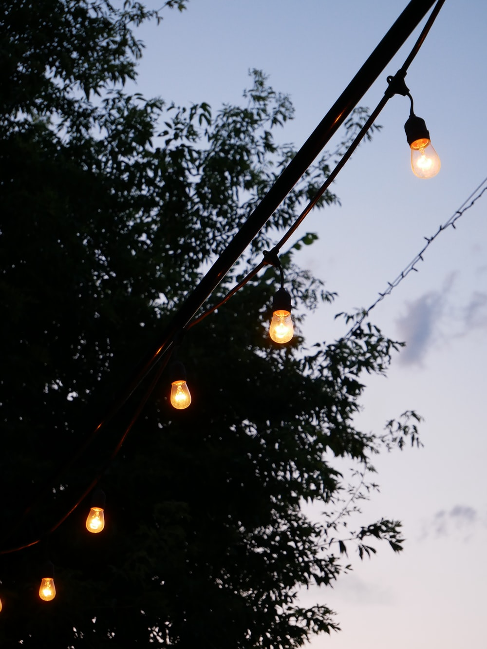 black metal post with string lights during night time