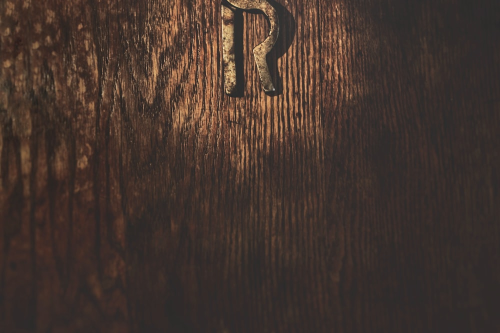 silver letter b on brown wooden table