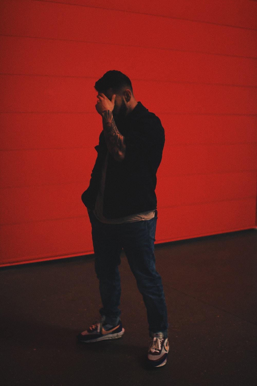 man in black long sleeve shirt and blue denim jeans standing beside orange wall