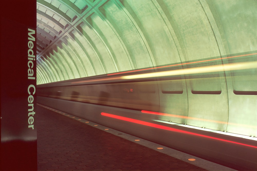 red and white train in a tunnel
