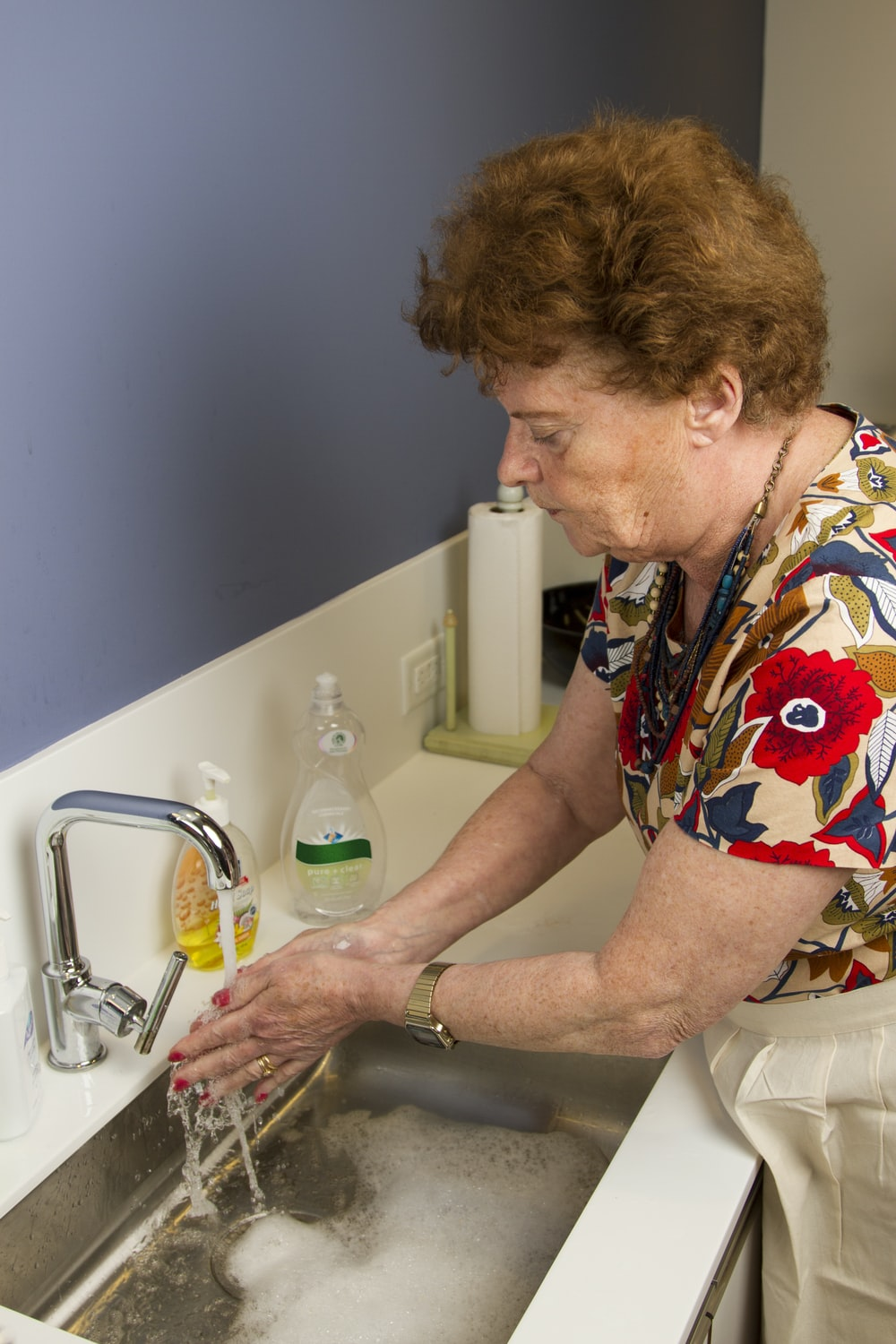 woman in red yellow and blue floral shirt sitting on white ceramic sink