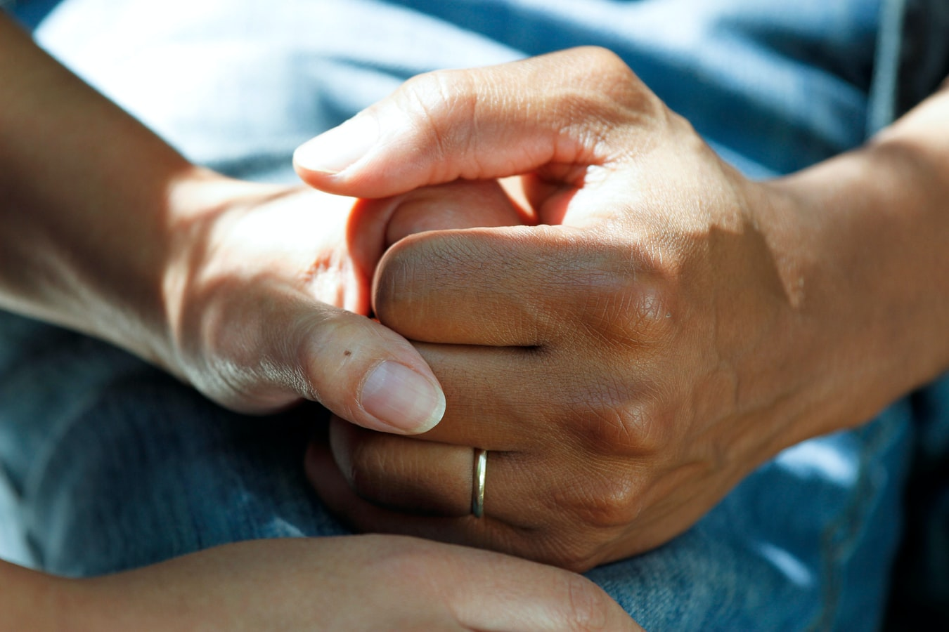 close-up of a man's hand (wearing a wedding band) squeezing a woman's hand for comfort