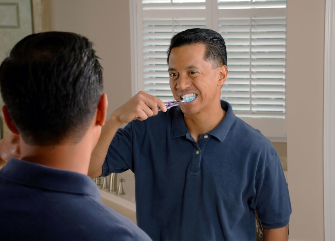 An Asian man brushing his teeth while looking in a mirror.
