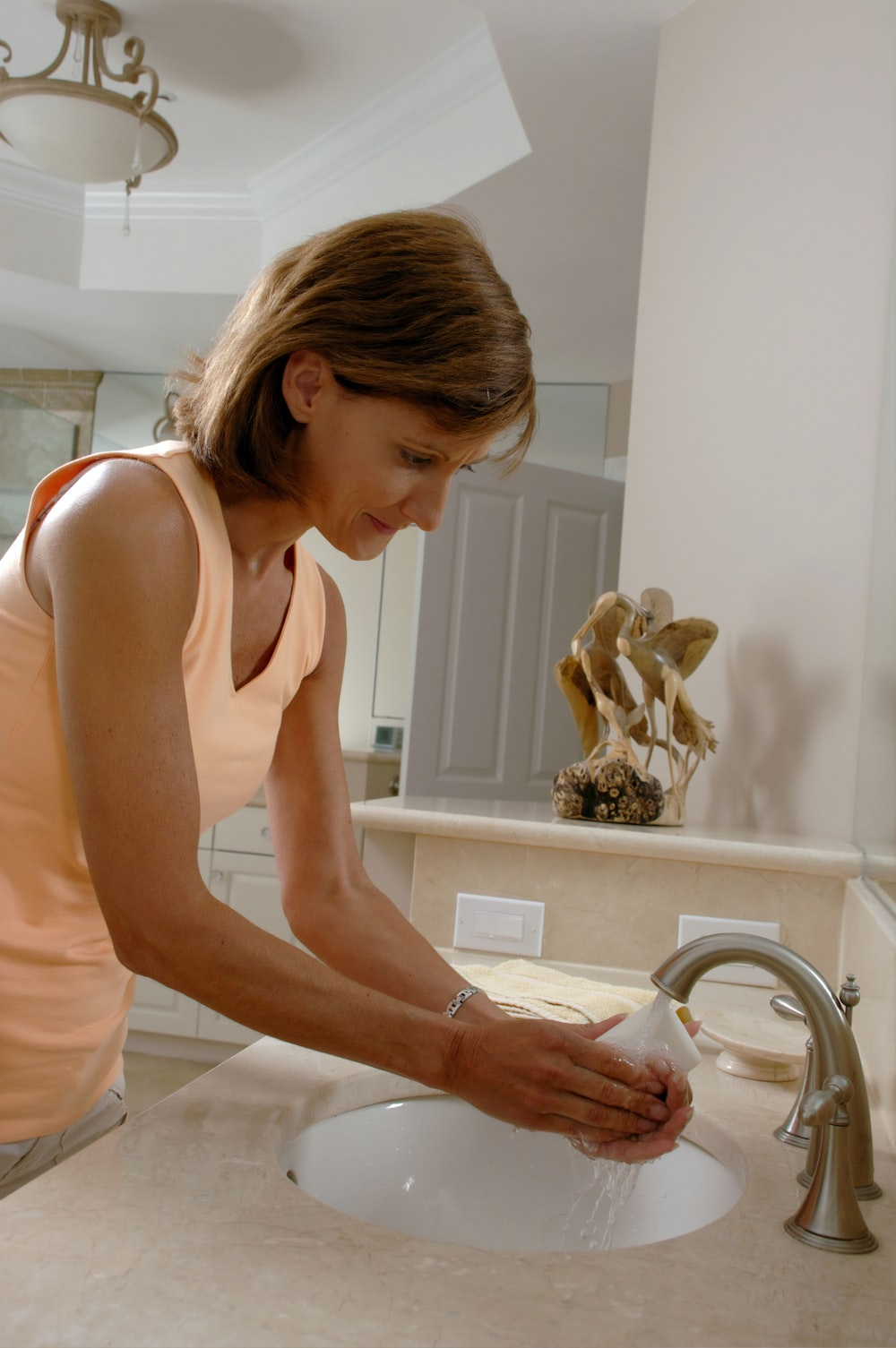 woman in white tank top holding white ceramic sink