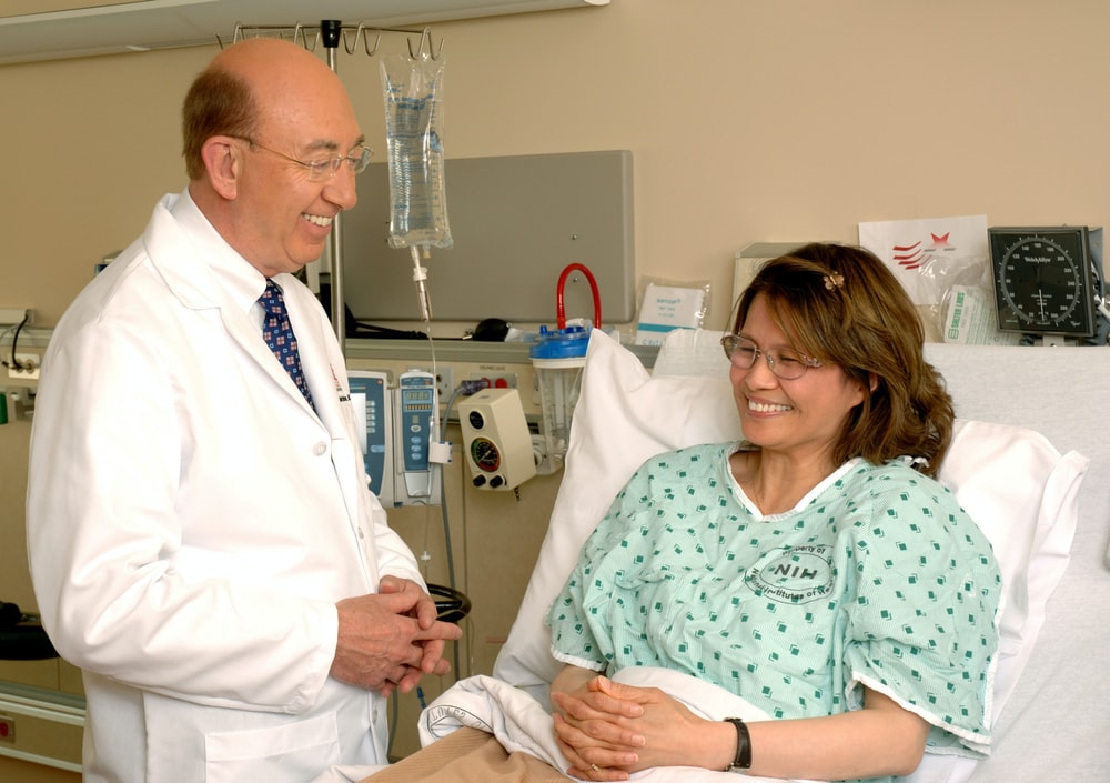 woman in teal scrub suit sitting beside man in white medical scrub suit