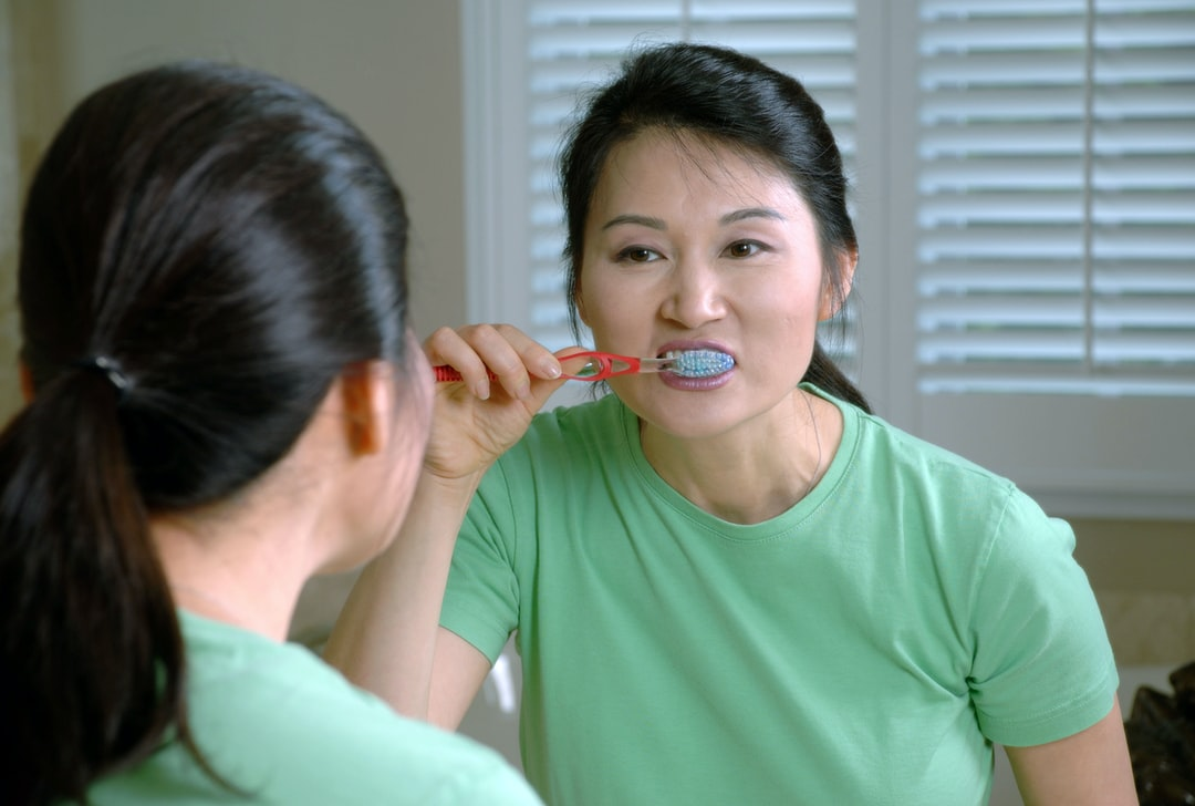 An Asian woman brushing her teeth while looking in the mirror.