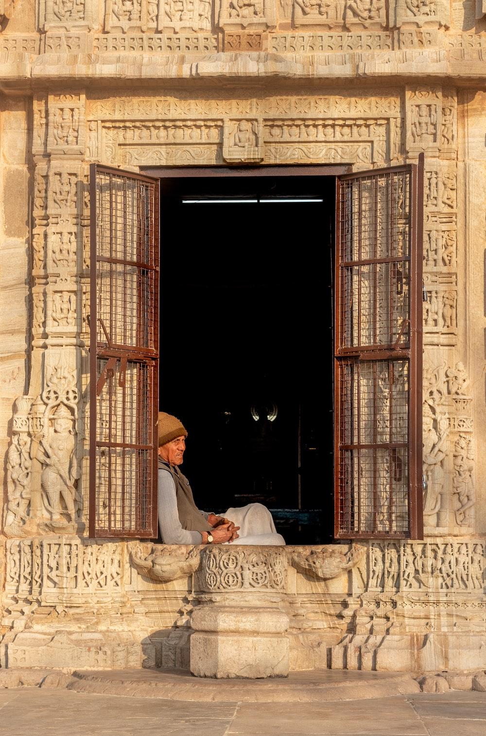 man in white thobe sitting on white chair near brown wooden door