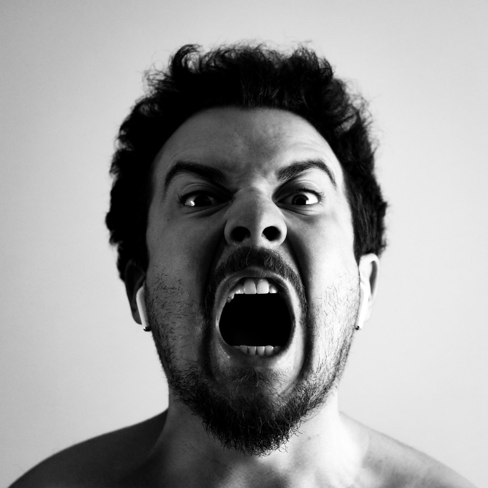 grayscale photo of man with mouth open