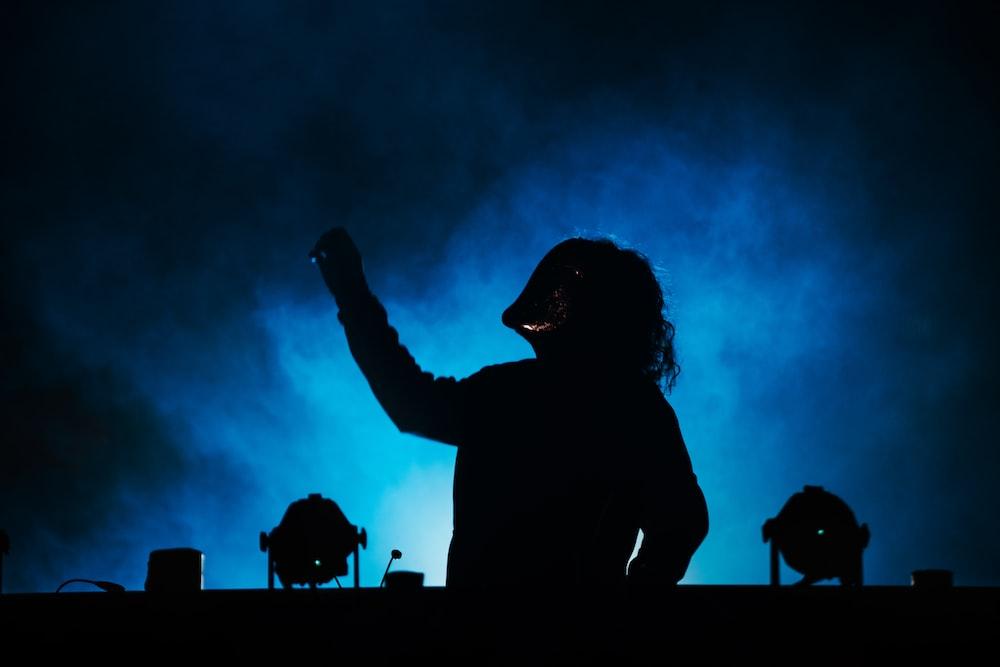 silhouette of man raising his hands