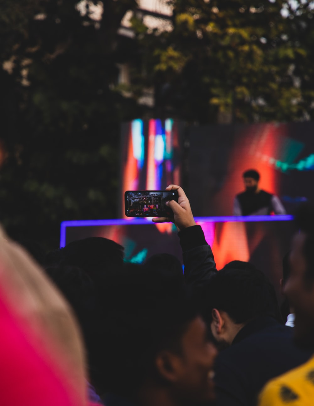 person holding smartphone taking photo of people in concert during night time