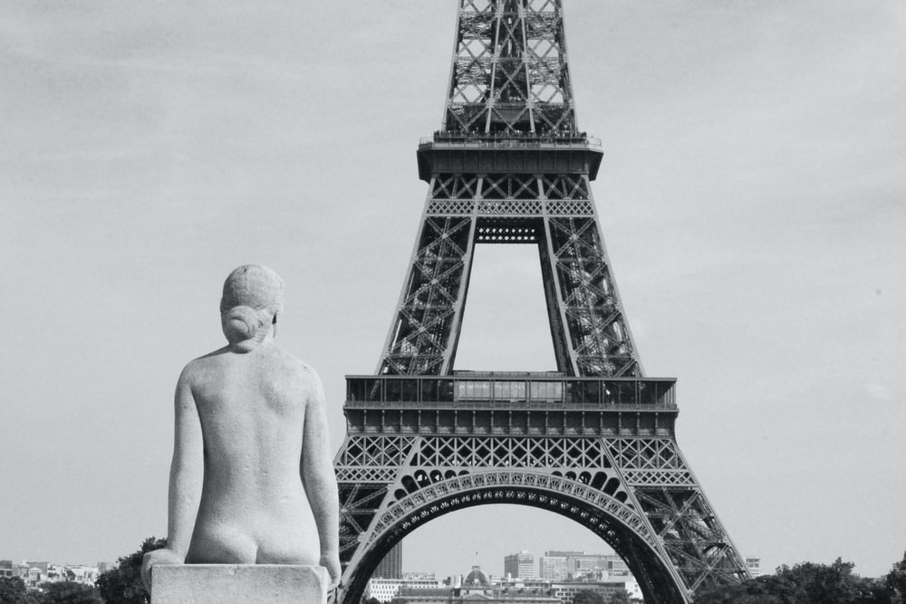 topless man standing near eiffel tower in grayscale photography