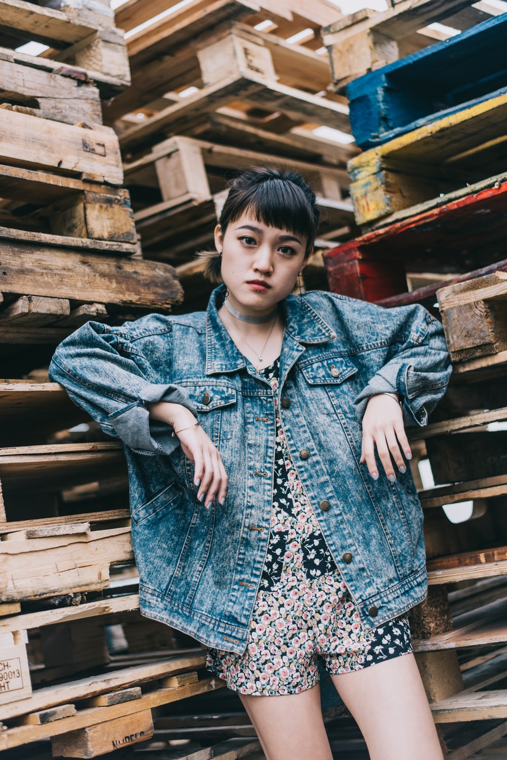 woman in blue denim jacket standing near brown wooden pallet