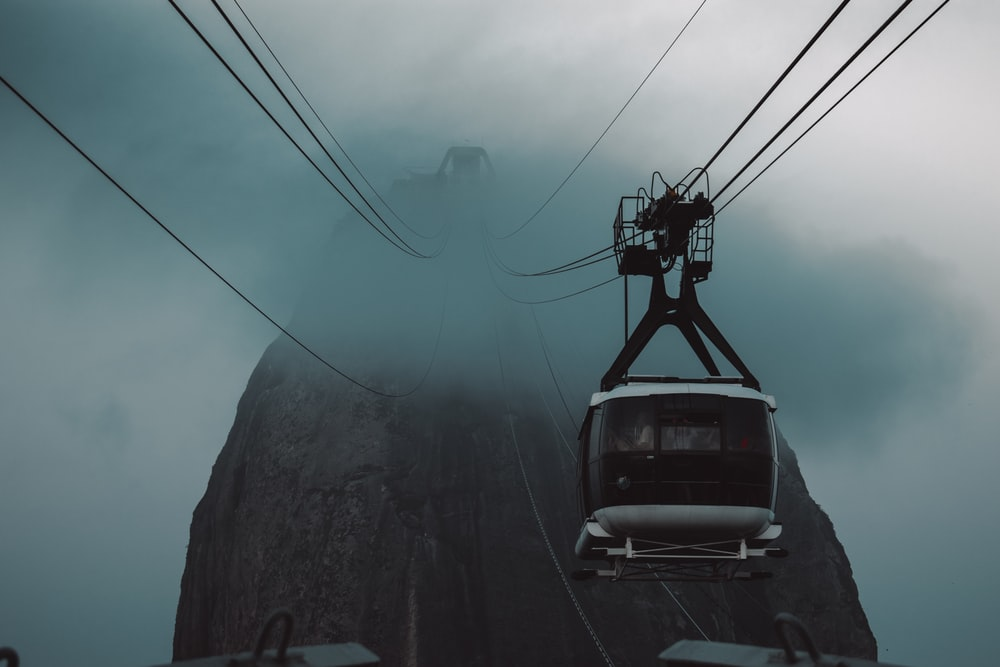blue car on black metal cable wire under white clouds