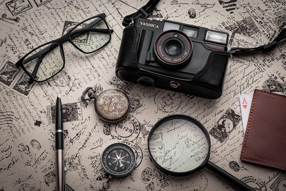 black nikon dslr camera beside black framed eyeglasses and black framed eyeglasses