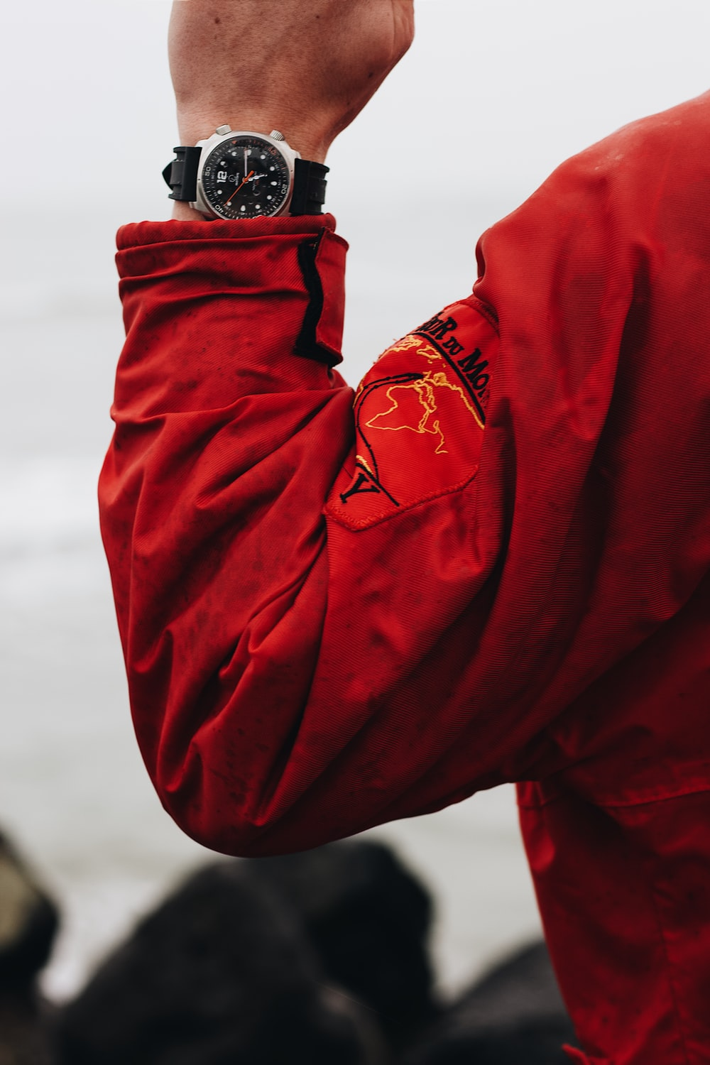 person in red jacket wearing black and silver watch