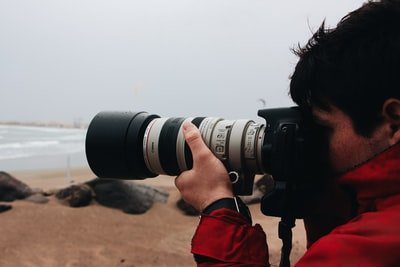 man in red jacket holding black dslr camera photo zoom background
