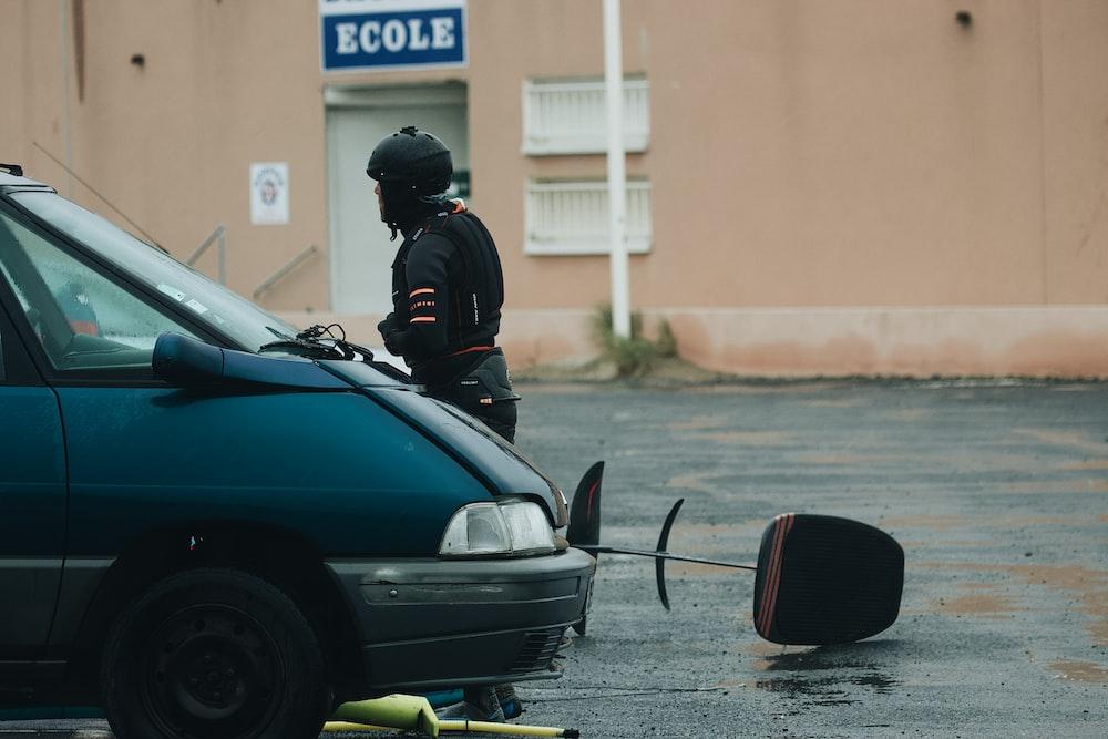 man in black helmet and black helmet riding on black car during daytime