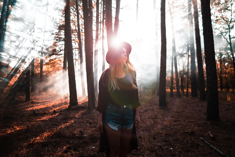 woman in green tank top and blue denim shorts standing in the woods during daytime