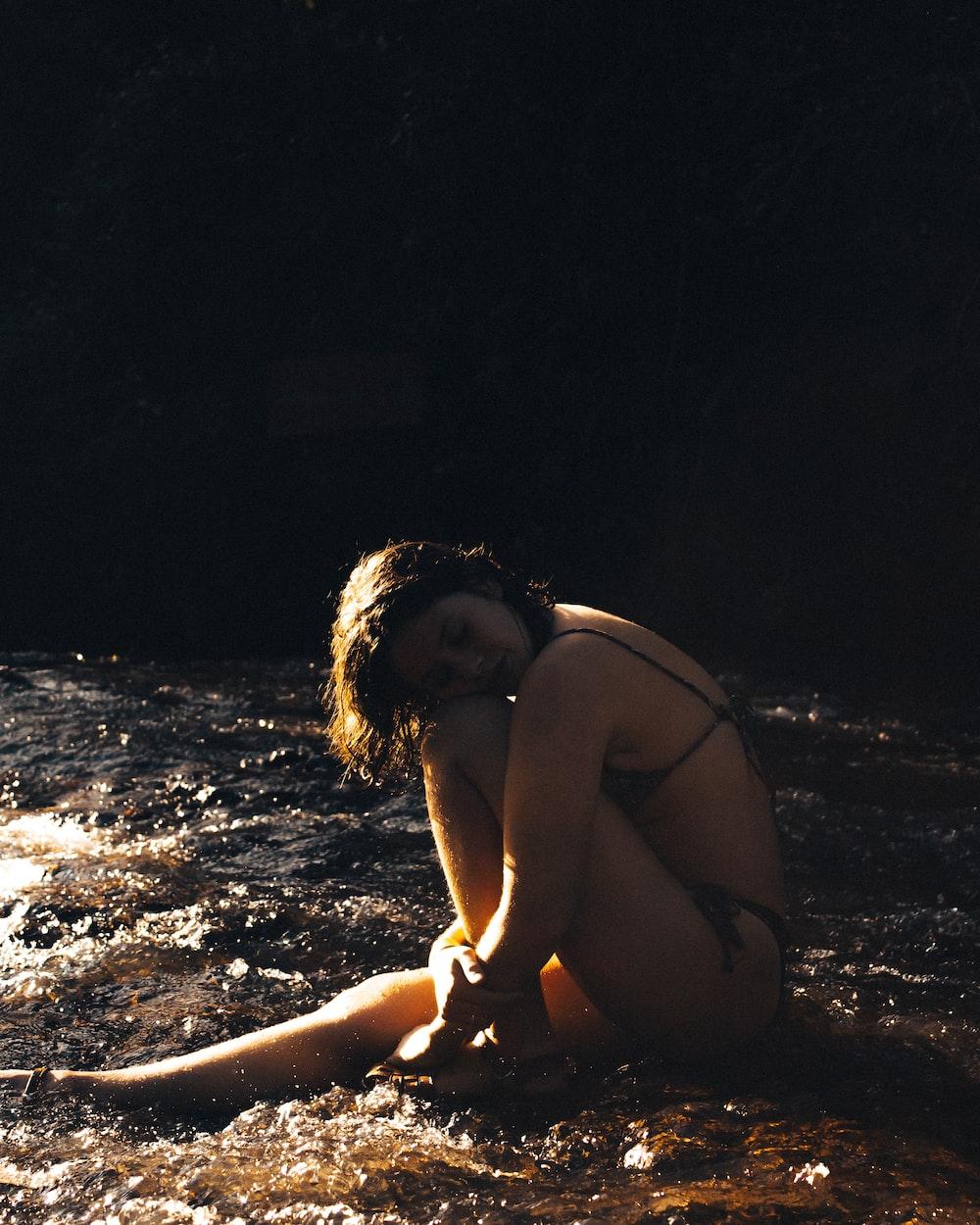 woman in black bikini sitting on sand during night time