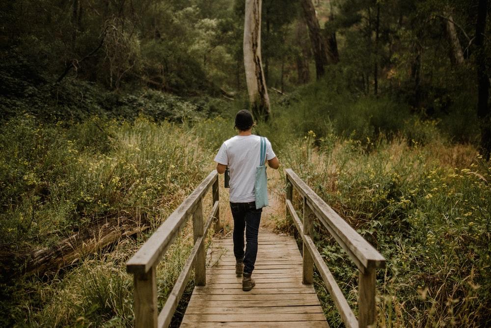 man in white shirt walking on wooden bridge