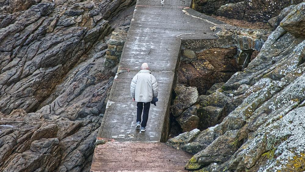 man in white jacket walking on gray concrete bridge during daytime