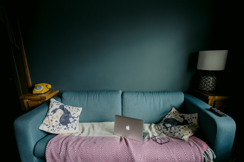 silver macbook on white and pink floral pillow