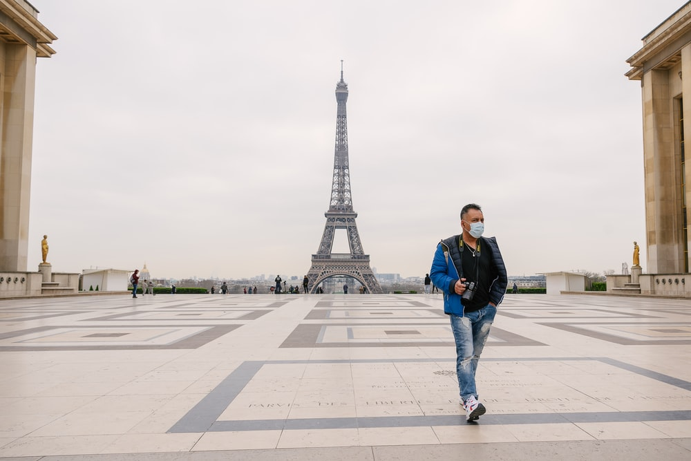 man in black jacket and blue denim jeans standing on gray concrete floor near eiffel tower