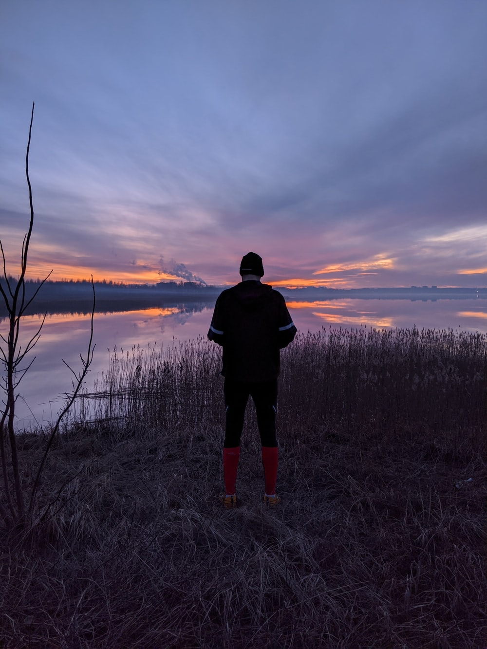 man in black jacket standing on grass field near lake during sunset