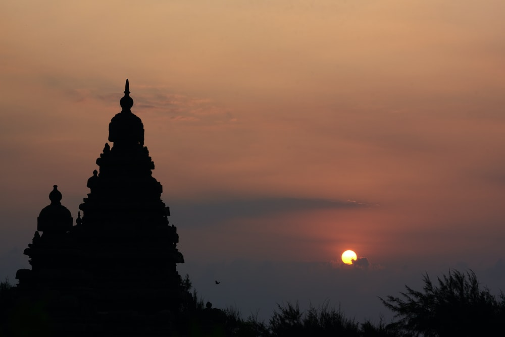 silhouette of buddha statue during sunset