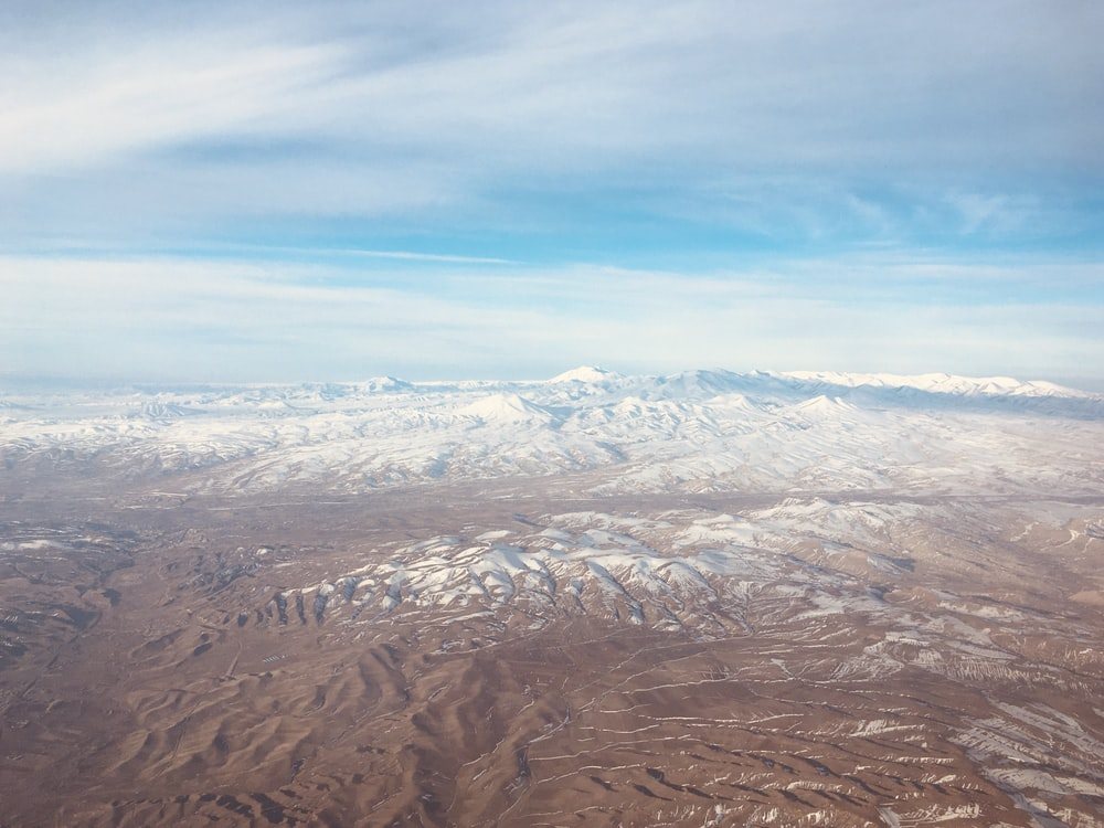 aerial view of brown mountains under blue sky during daytime