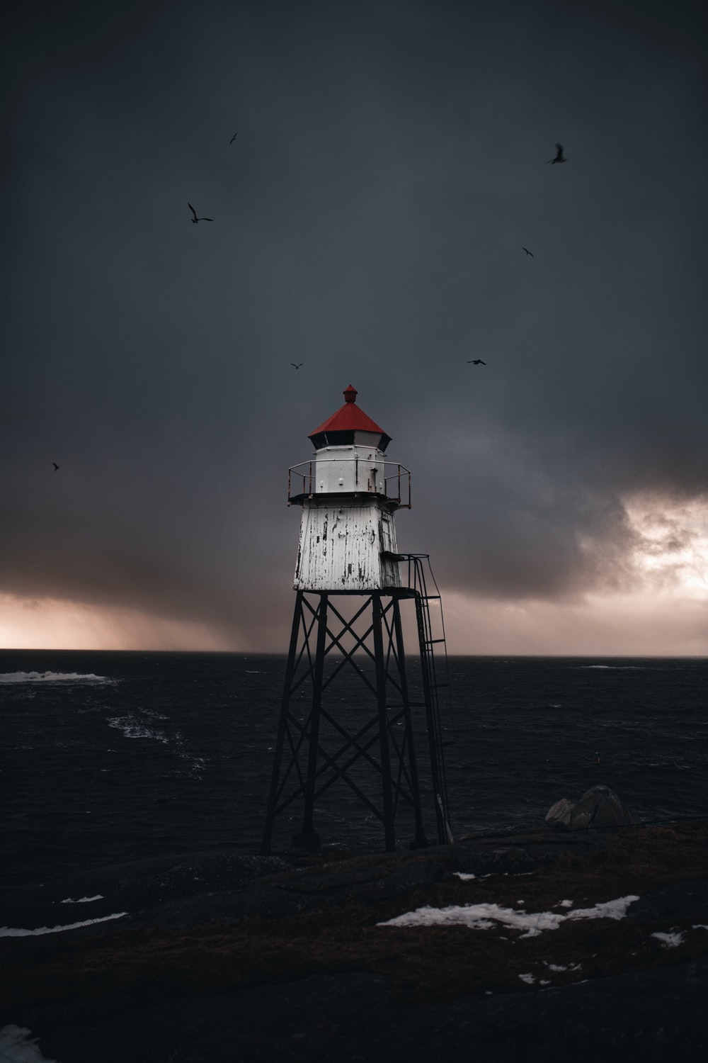 white and red lighthouse on sea during sunset