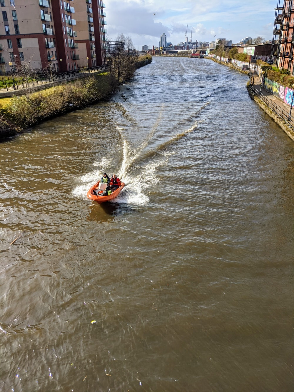 man in red life vest riding red and white inflatable boat on river during daytime