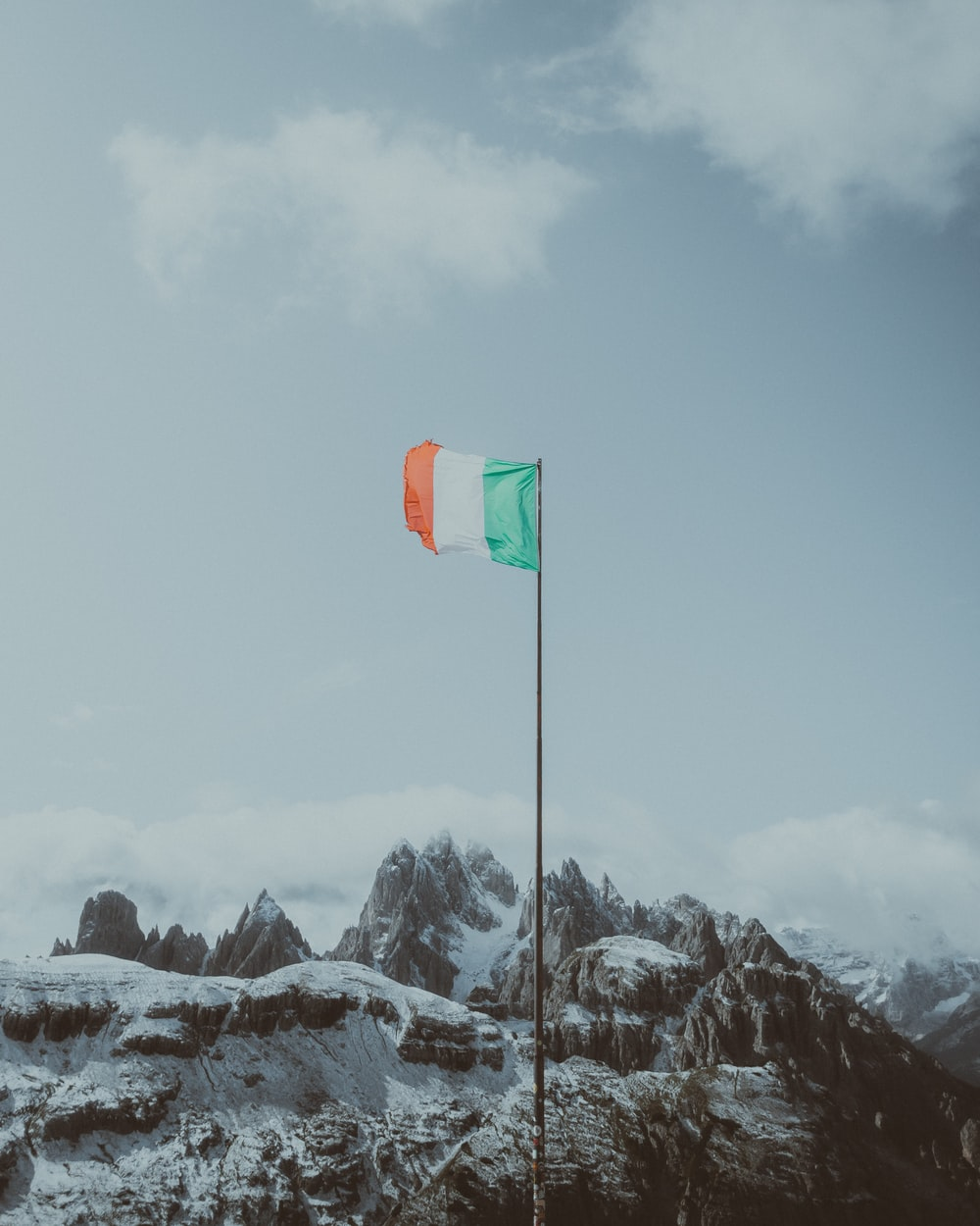 green flag on snow covered mountain during daytime