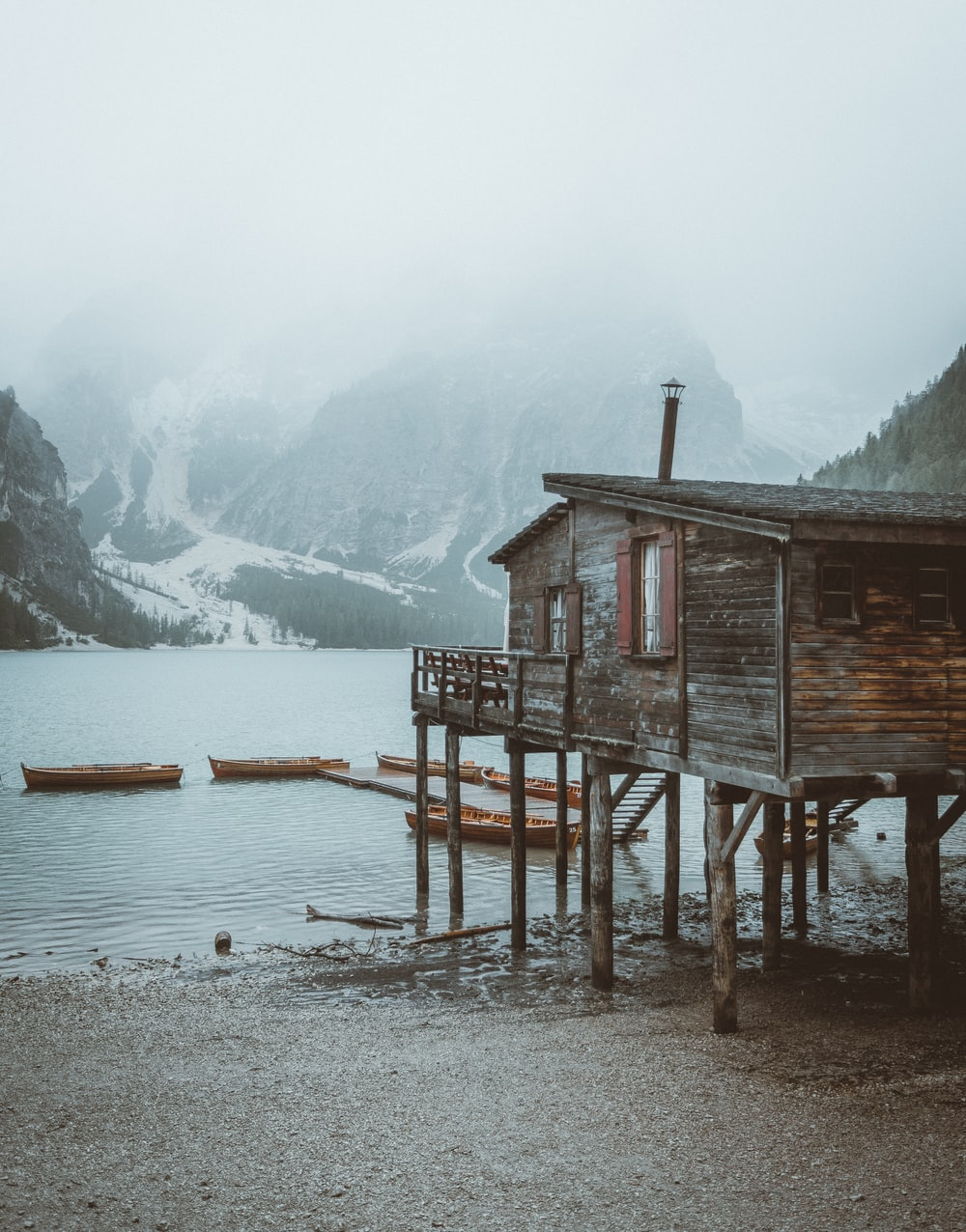 brown wooden house on body of water near snow covered mountain during daytime