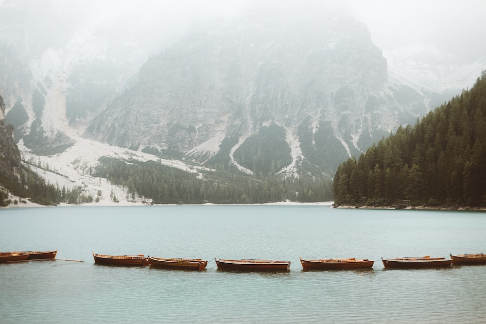 brown wooden boat on body of water near mountain during daytime