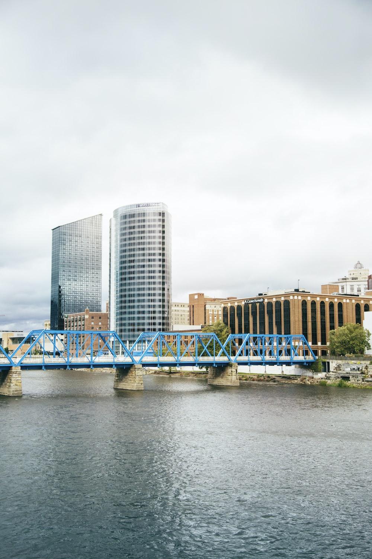 blue bridge over river near city buildings during daytime