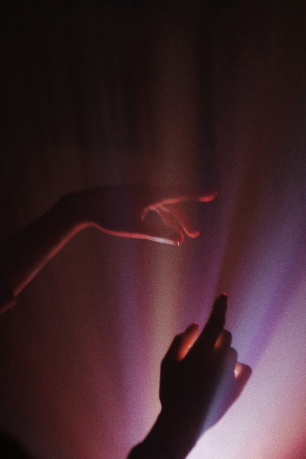 person holding red light in dark room