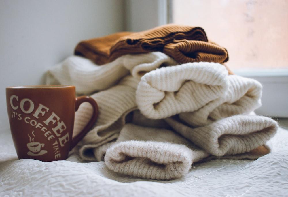 white and brown ceramic mug on white textile