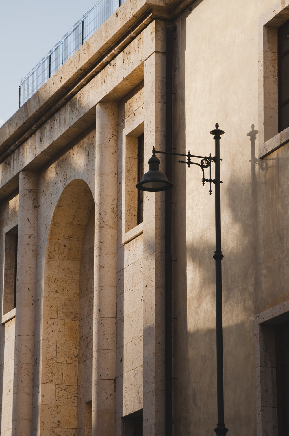 black sconce lamp on brown concrete building