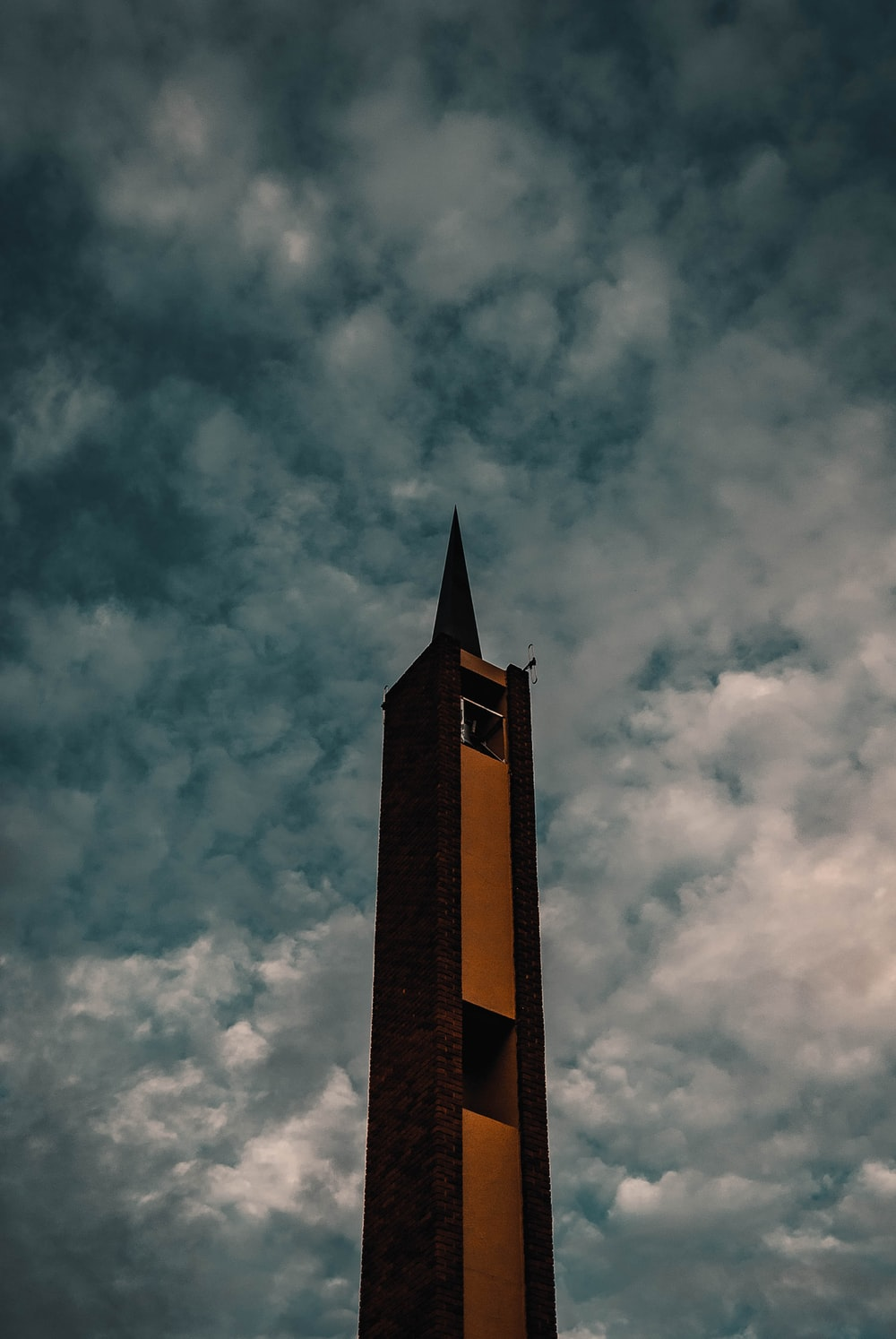 brown concrete tower under cloudy sky during daytime