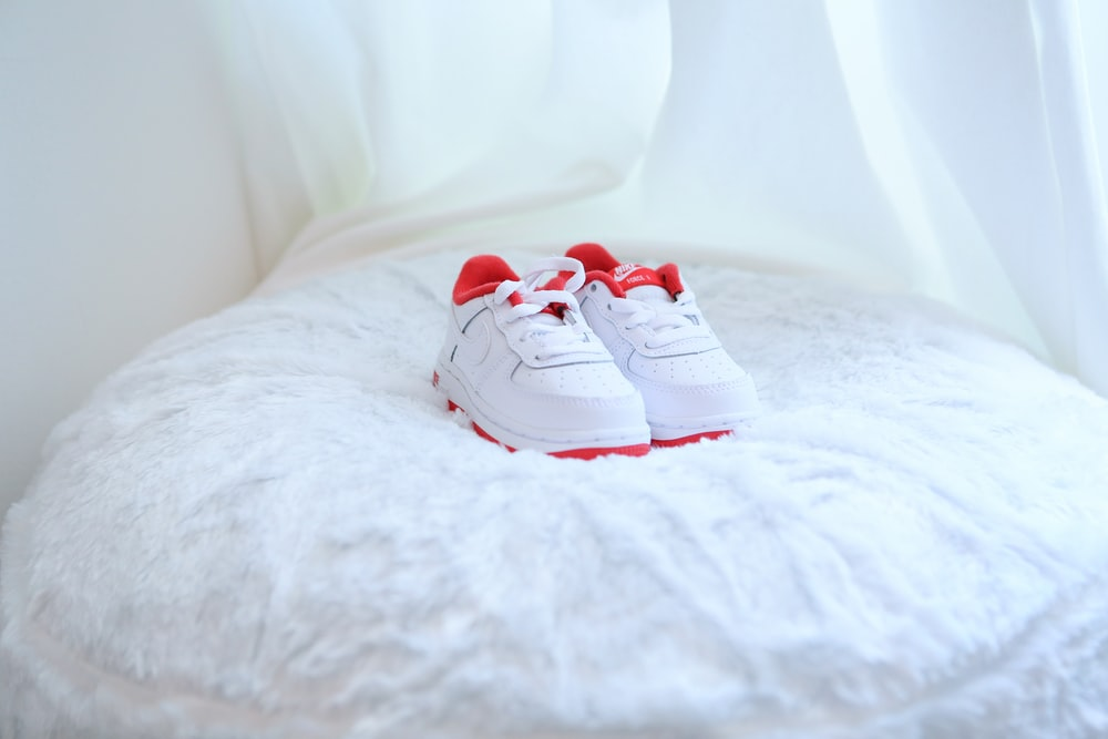 white and red nike sneakers on white textile