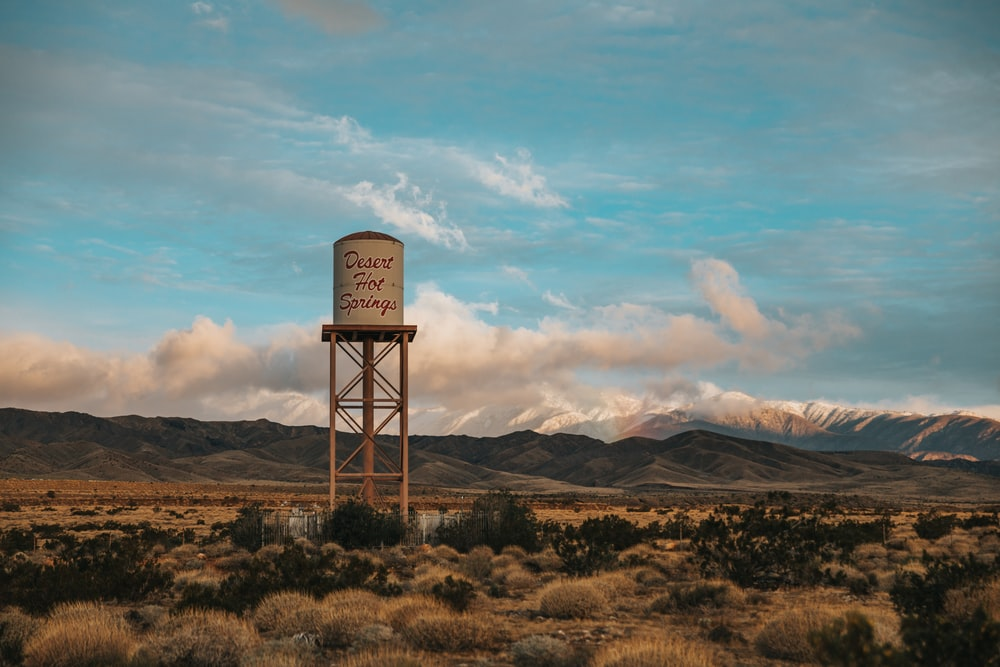 gray steel water tank on brown grass field under white cloudy sky during daytime