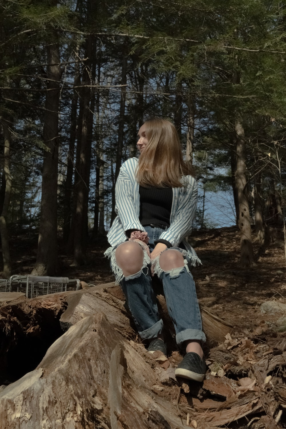 woman in white long sleeve shirt and blue denim jeans sitting on brown log during daytime