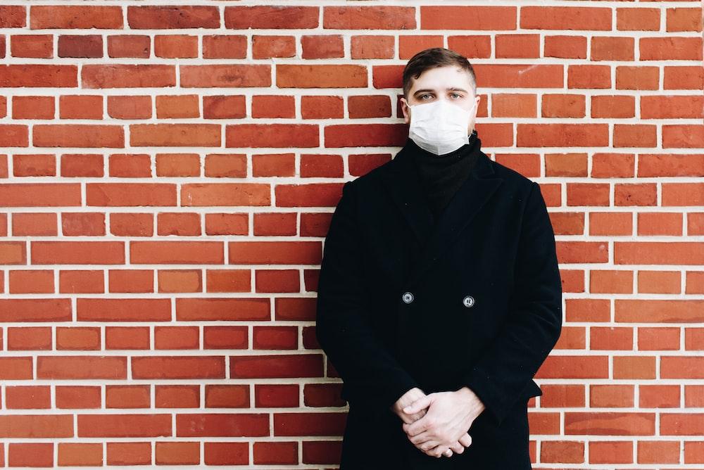 man in black coat standing beside brown brick wall