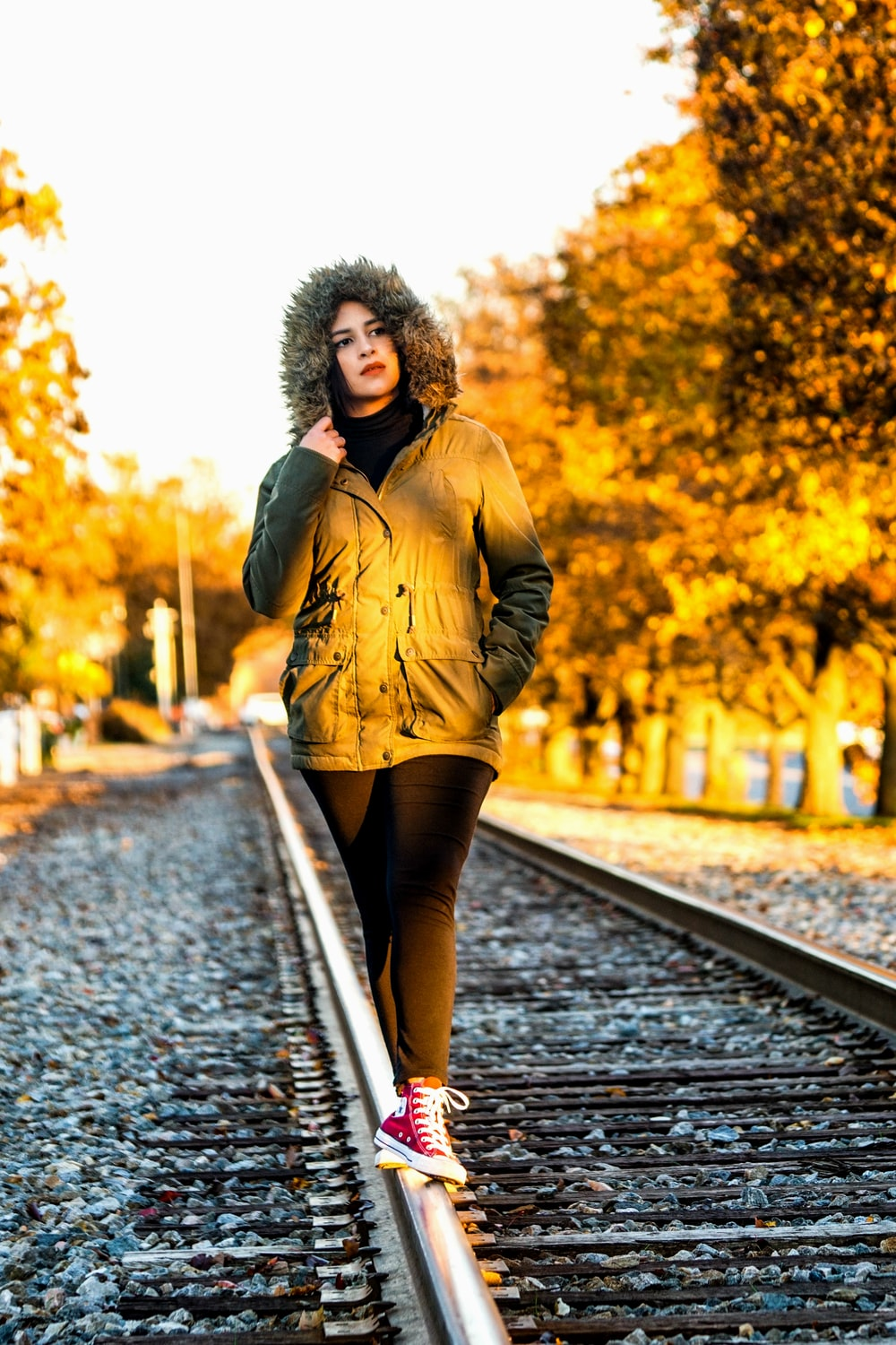 woman in brown coat standing on pathway during daytime